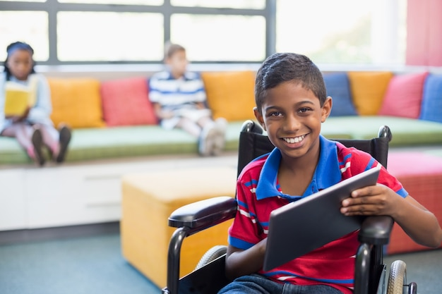 Scolaro disabile sulla sedia a rotelle facendo uso della compressa digitale nella biblioteca