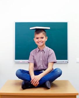 Scolaro felice con il libro sulla testa che si siede nella posa del loto nella stanza di classe sulla tavola.