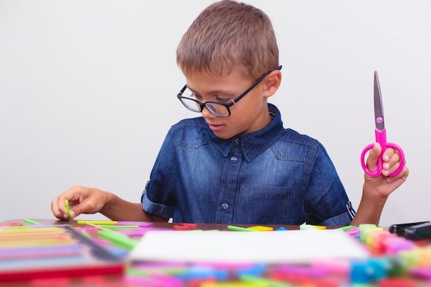 Scolaro in una camicia blu che si siede al tavolo. ragazzo con gli occhiali concetto torna a scuola
