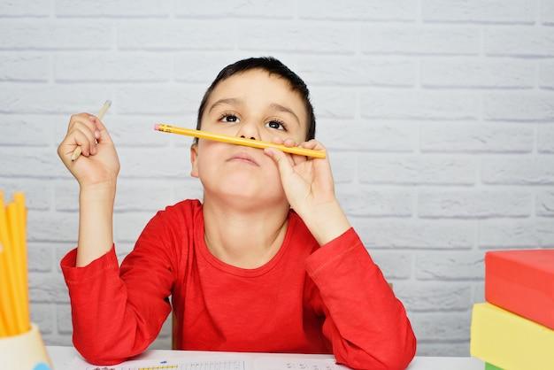 Scolaro noioso turbato che fa i compiti. istruzione, scuola, concetto di difficoltà di apprendimento.