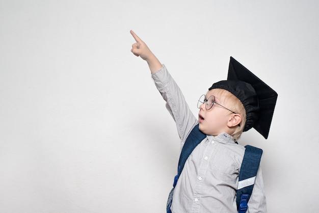 Scolaro sorpreso in abito, occhiali e cappello accademico punta il dito verso l'alto. concetto di scuola. sfondo bianco.