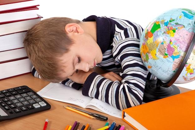Scolaro stanco sta dormendo su uno sfondo bianco