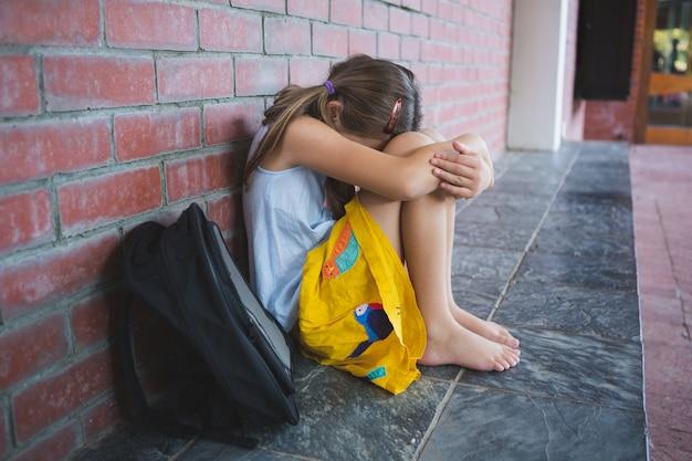 Scolaro triste seduto da solo in corridoio