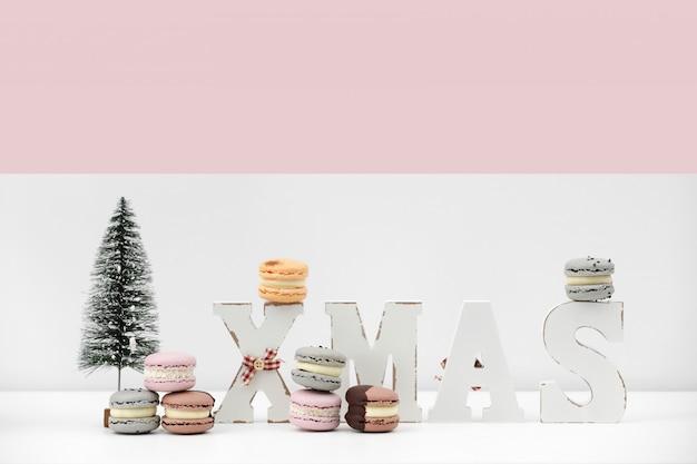 Scolpisca i maccheroni o i macarons del dessert su fondo bianco e rosa di natale con natale dell'iscrizione. concetto di ricetta di cibo. copia spazio.