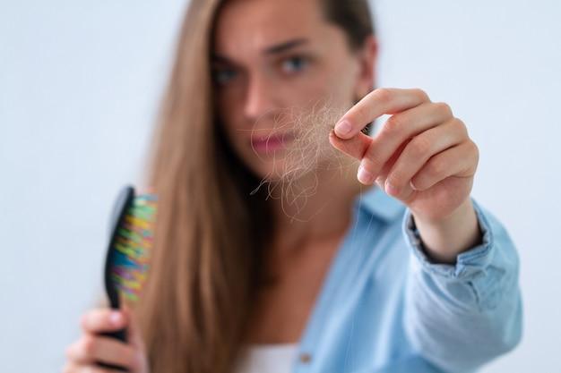 Sconvolta la donna stressata con il pettine che ha un problema di capelli e soffre di perdita di capelli