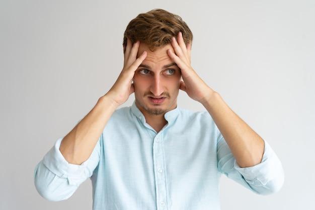 Sconvolto confuso ragazzo sentendosi in colpa. giovane uomo caucasico bello che tiene testa
