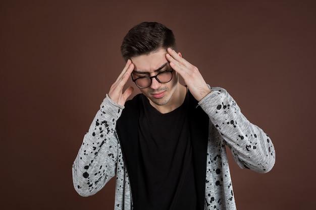 Sconvolto infelice giovane stringendo la testa con le mani, che soffrono di mal di testa. concetto di persone, stress, tensione ed emicrania
