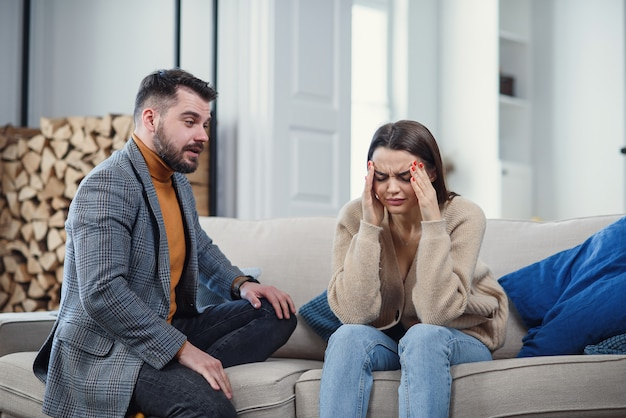 Sconvolto la coppia a casa. l'uomo bello e la bella giovane donna stanno avendo litigio. seduti insieme sul divano. problemi familiari.