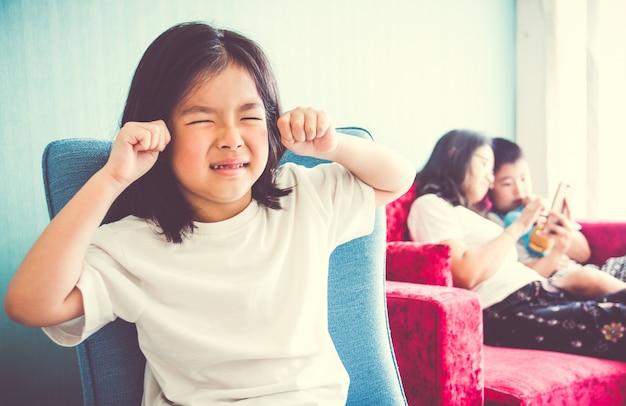 Sconvolto ragazza seduta sulla sedia madre godendo con il fratello sul divano a casa