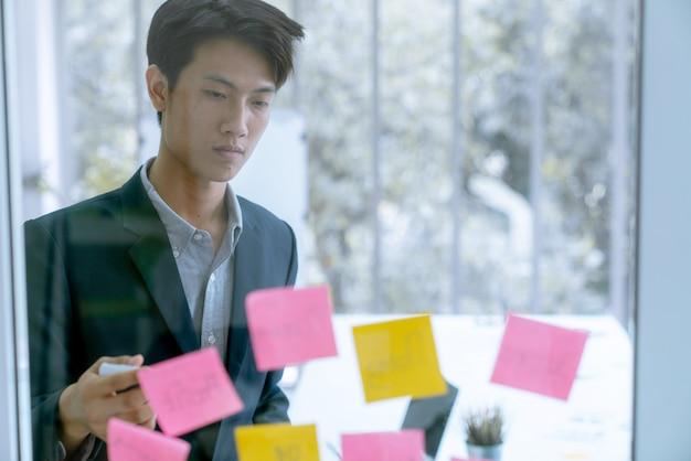 Scopo asiatico dell'obiettivo del piano di lavoro dell'uomo di affari della società con carta per appunti sul vetro della parete