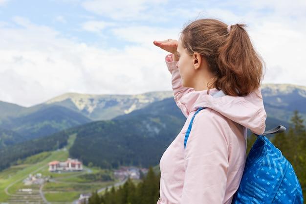 Scopri e viaggia concetto. fotografia della vista della ragazza con la mano vicino al viso, in posa su cielo blu e montagne