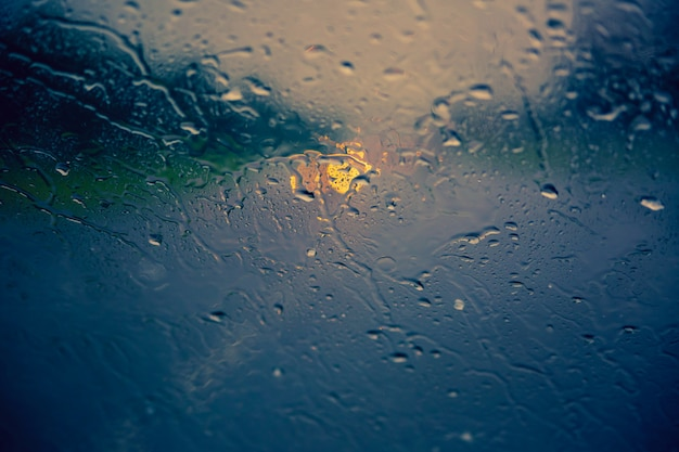 Scorre gocce di pioggia sul parabrezza dell'auto. concetto di caduta. sfondo