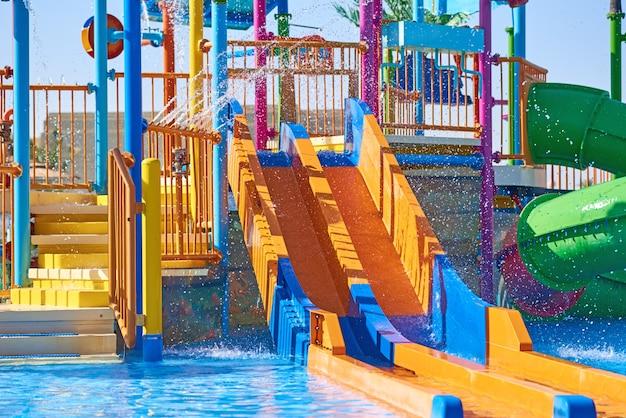 Scorrevoli variopinti nella fine del waterpark su. cursori aquapark con piscina