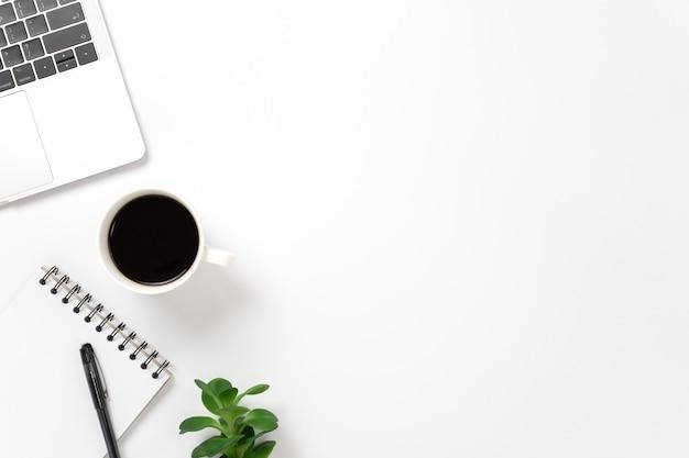Scorri laici, scrivania da tavolo vista dall'alto con smartphone, tastiera, caffè, matita, foglie con spazio di copia.