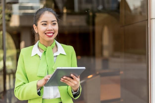 Scort donna con tablet e cellulare sorridente