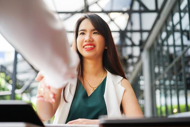 Scossa della mano della donna asiatica del responsabile con la persona laureata dopo il colloquio di lavoro