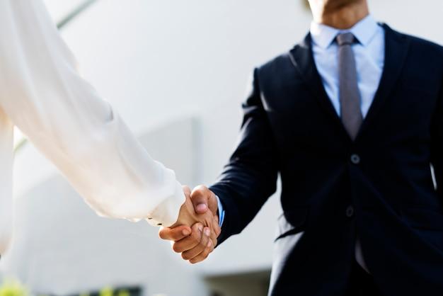 Scossa delle mani di accordo di affari delle donne degli uomini