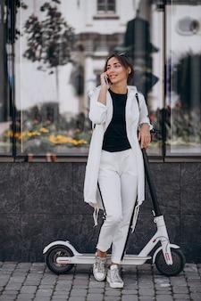 Scotter di guida della giovane donna in città e per mezzo del telefono