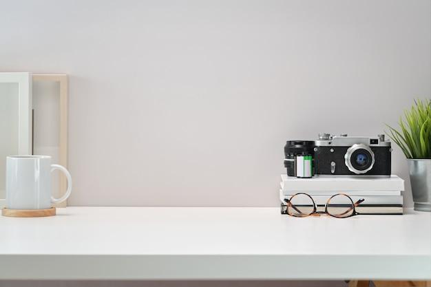 Scrittoio bianco dell'area di lavoro scandinava con macchina fotografica d'epoca, film, poster e copia spazio