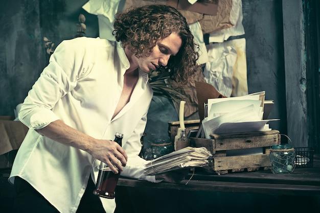 Scrittore al lavoro. bel giovane scrittore in piedi vicino al tavolo e inventando qualcosa nella sua mente