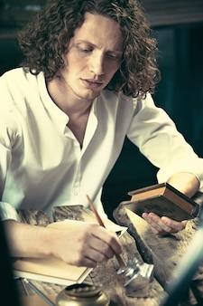 Scrittore al lavoro. bel giovane scrittore seduto al tavolo e scrivere qualcosa nel suo blocco per schizzi