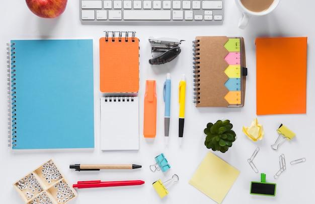 Scrittorio creativo bianco dello spazio di lavoro con i rifornimenti per ufficio colourful