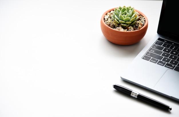 Scrittorio dell'area di lavoro con il computer portatile e concetto di affari e tecnologia