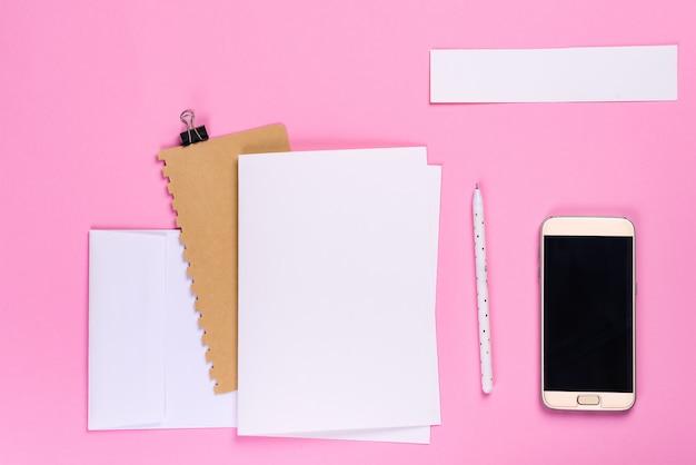 Scrittorio dell'area di lavoro con lo smartphone e taccuino con copyspace su fondo rosa, disposizione piana di stile minimo