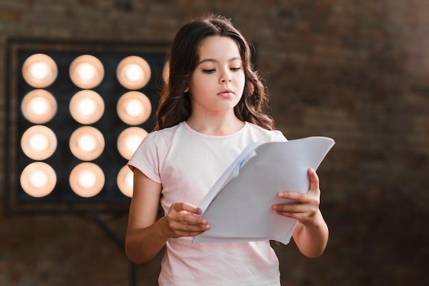 Scrittorio della lettura della ragazza che sta contro la luce della fase