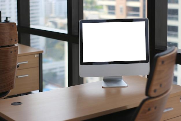 Scrittorio di legno della tavola nella stanza di affari dell'ufficio con il grande monitor del computer e fondo delle finestre