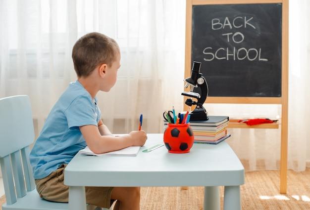 Scrittorio di seduta dell'aula domestica di seduta del ragazzo di scuola riempito di materiale di addestramento dei libri scolaretto che dorme annoiato pigro
