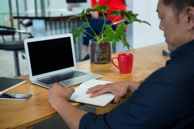 Scrittorio di seduta dell'uomo d'affari che esamina diario