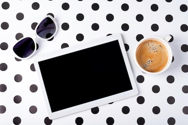Scrittorio femminile con la compressa, tazza di caffè, occhiali da sole sulla vista superiore del fondo creativo