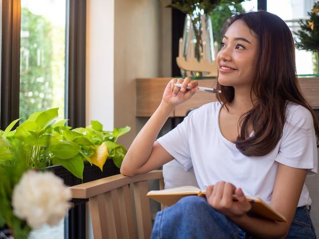 Scrittrice seduta e che pensa alla storia che sarebbe stata scritta nel suo manuale felicemente sorridere.