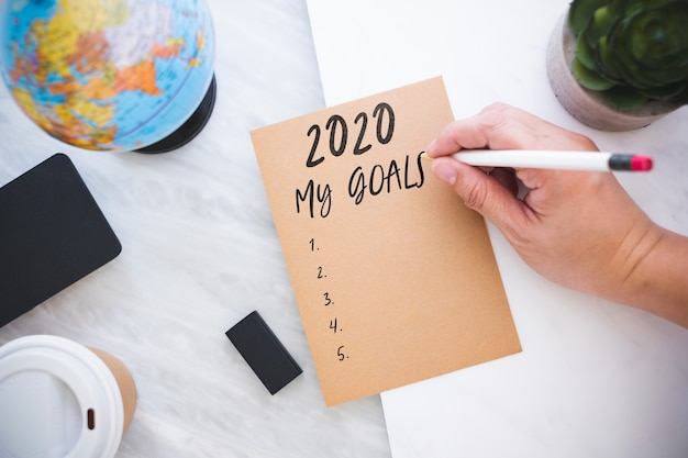 Scrittura a mano 2020 i miei obiettivi su carta marrone con globo blu, lavagna, tazza di caffè sul tavolo di marmo