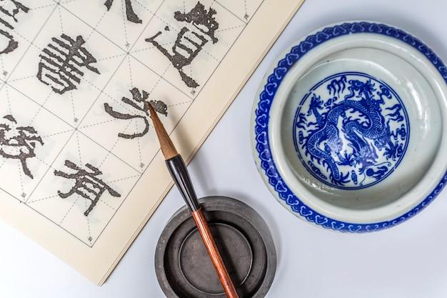 Scrittura a mano di pennello inchiostro della calligrafia della porcellana bianco