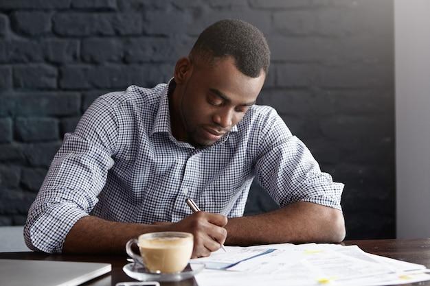 Scrittura a mano giovane lavoratore di ufficio africano laboriosa, compilando documenti mentre si fa la contabilità
