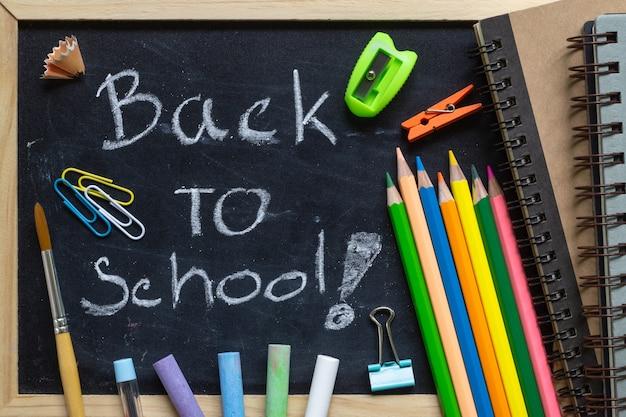 Scrittura a mano libera torna a scuola lettere sulla lavagna con materiale scolastico