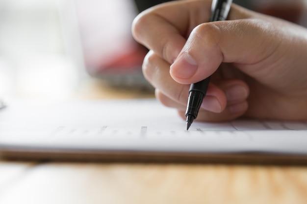 Scrittura a mano su un foglio con una penna