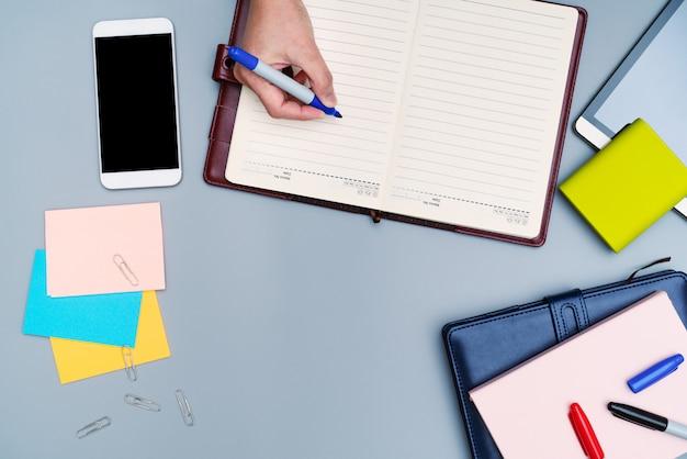 Scrittura a mano sul notebook circondato con accessori per ufficio.