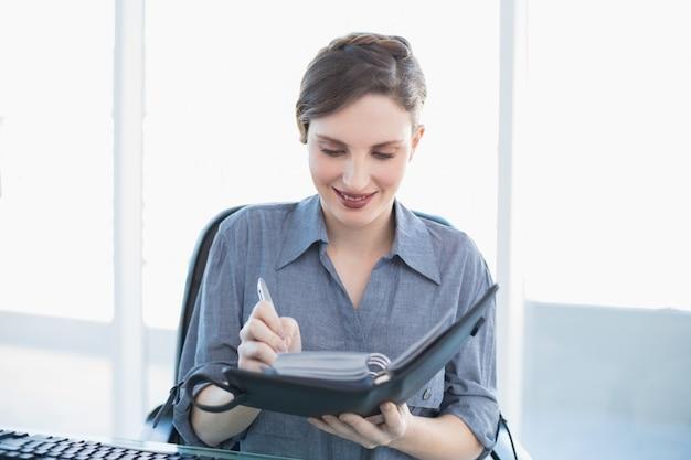 Scrittura allegra della donna di affari nel suo diario che si siede al suo scrittorio
