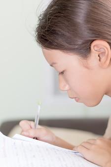 Scrittura asiatica della ragazza sul libro di lezione
