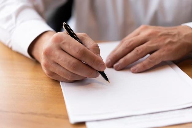 Scrittura corporativa dell'uomo sul documento in bianco