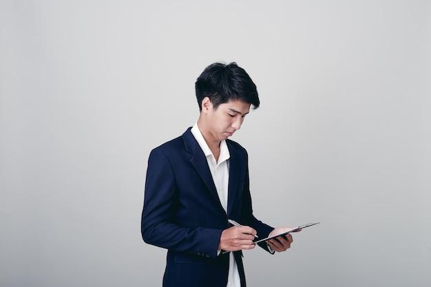Scrittura dell'uomo d'affari in taccuino su bianco
