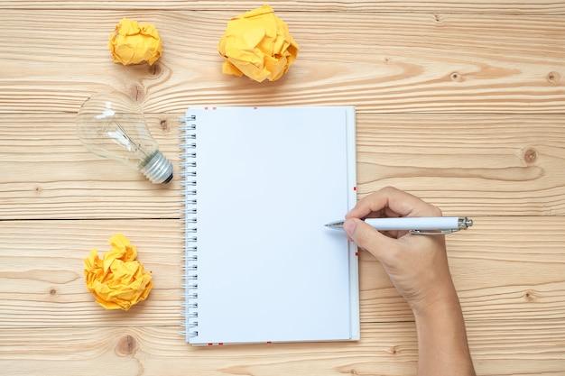 Scrittura dell'uomo d'affari sul taccuino con la lampadina e carta sbriciolata sulla tavola di legno