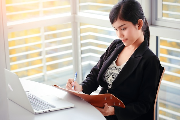 Scrittura della donna di affari sul taccuino con il computer portatile