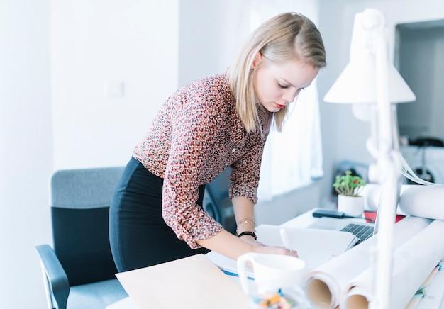 Scrittura della donna di affari sull'archivio sopra lo scrittorio in ufficio
