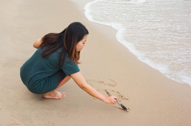 Scrittura della donna sulla spiaggia sabbiosa con il ramo di albero
