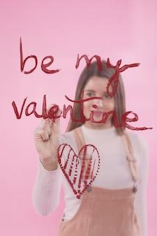 Scrittura della giovane donna sia il mio valentine su vetro con rossetto