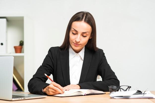 Scrittura della giovane donna sul diario con la matita nel luogo di lavoro nell'ufficio
